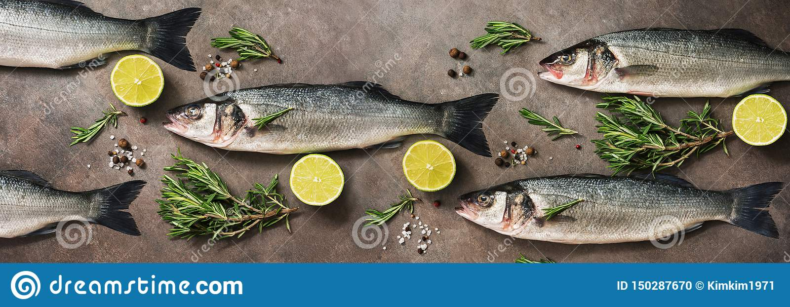 Fresh raw sea bass fish with rosemary and lime on a dark brown rustic background,banner. Flat lay, overhead view