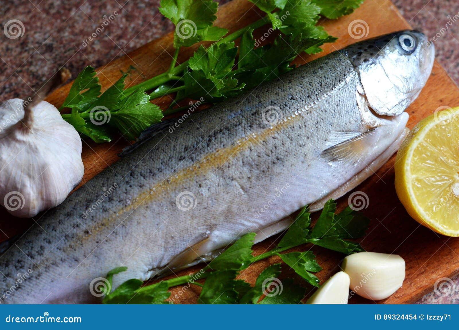 Fresh raw trout on kitchen board