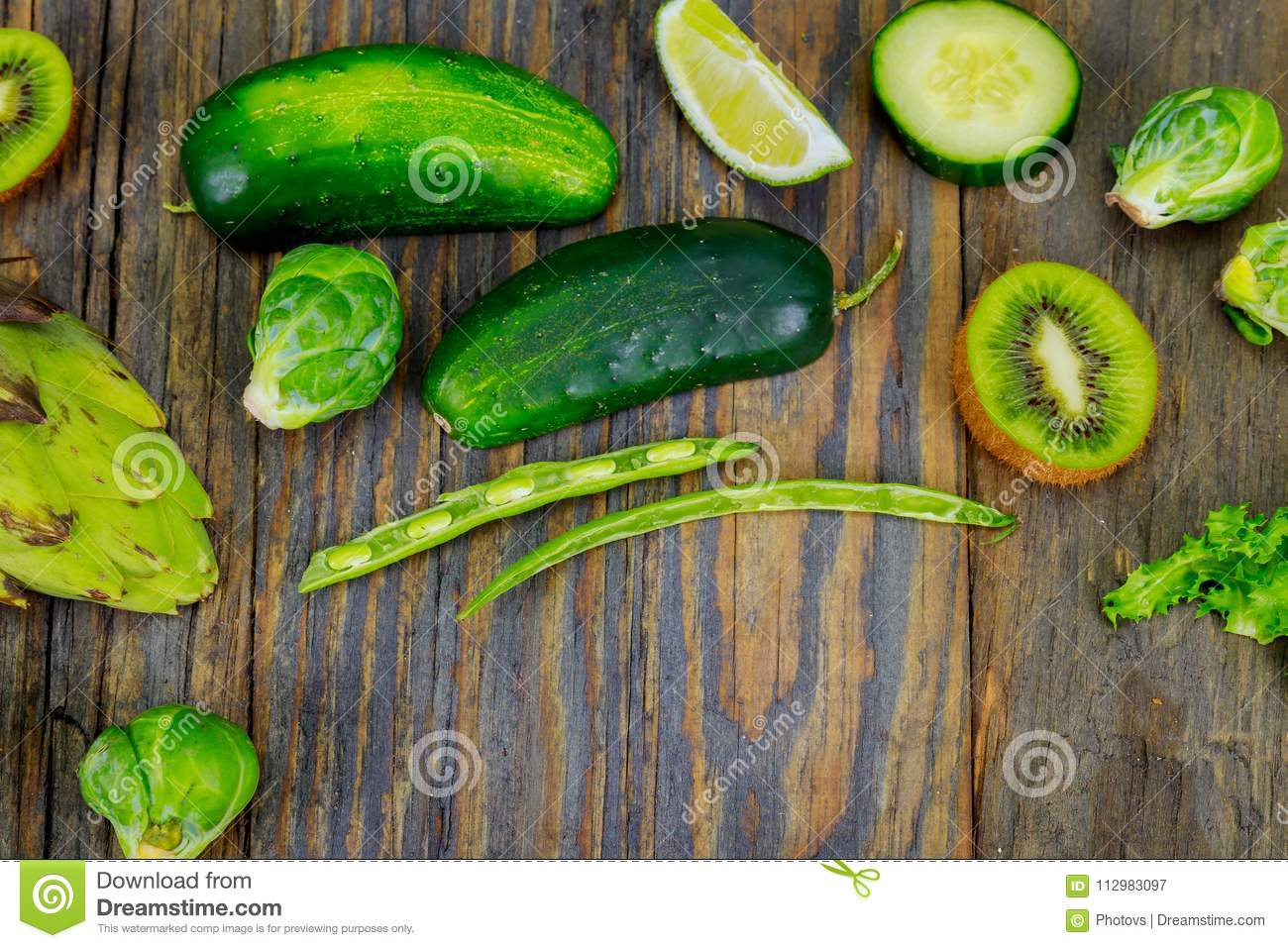 Fresh raw vegetable ingredients for healthy cooking or salad making with rustic olive wood board in center, top view, copy space.
