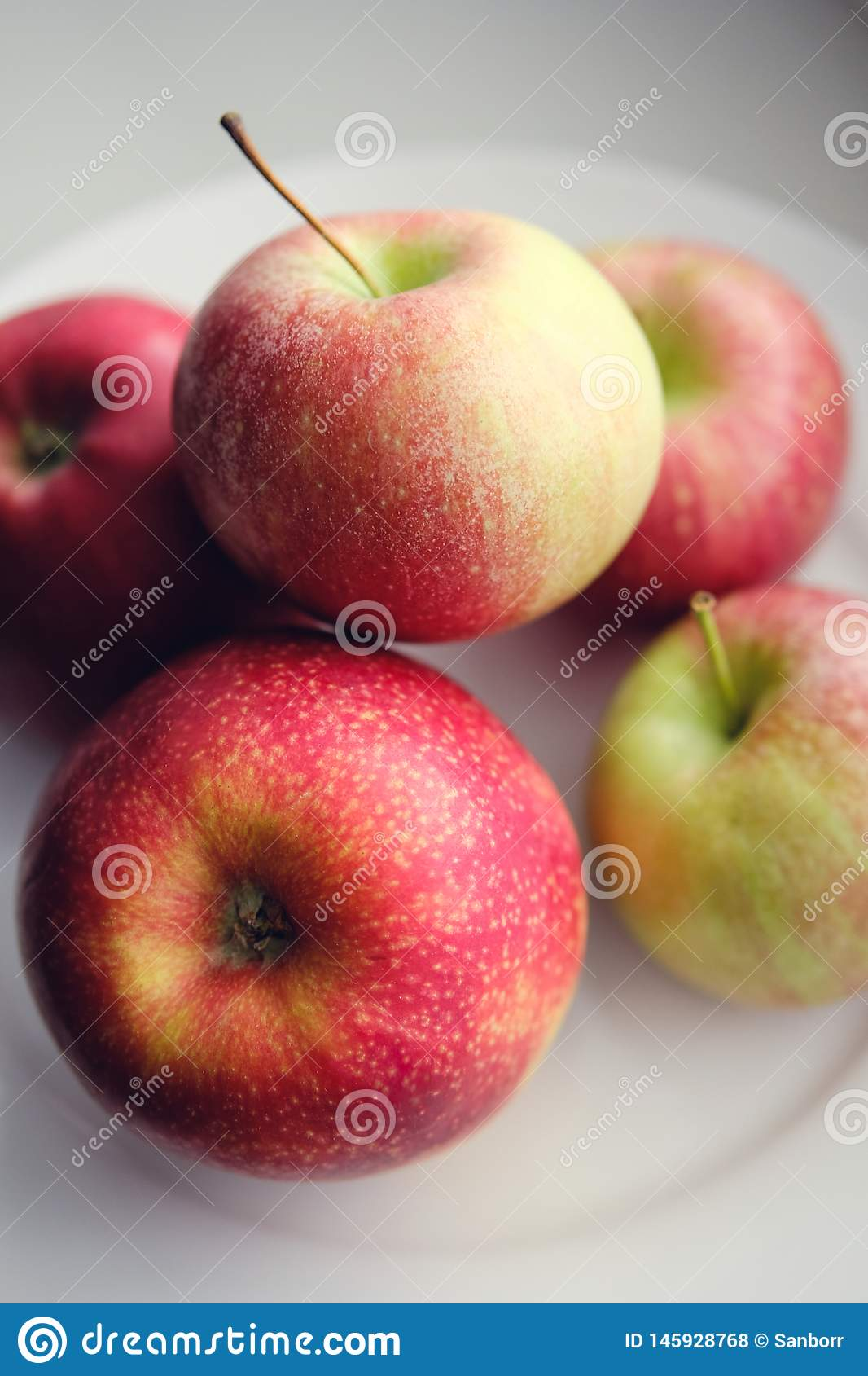 Fresh red apples on a white plate. Healthy diet