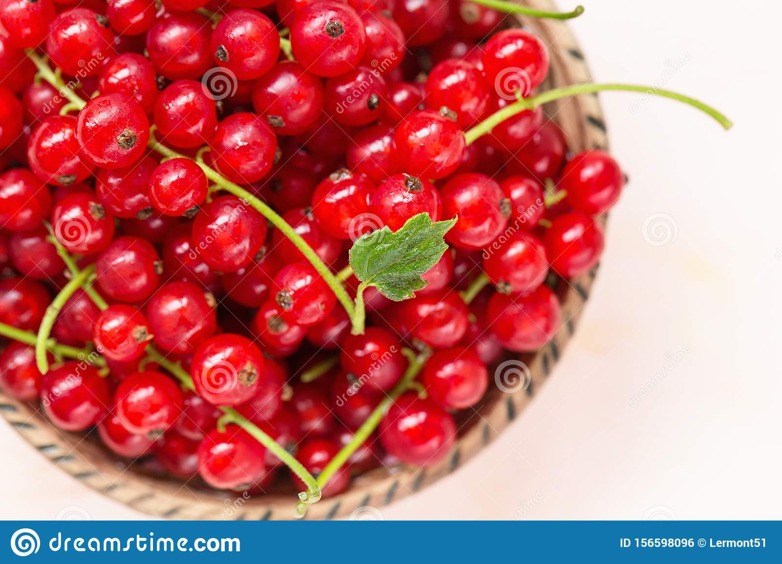 Fresh red currant berries in a bowl on a pink background