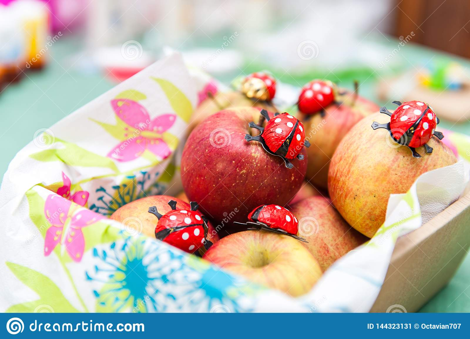 Fresh apples in basket with chocolate ladybugs