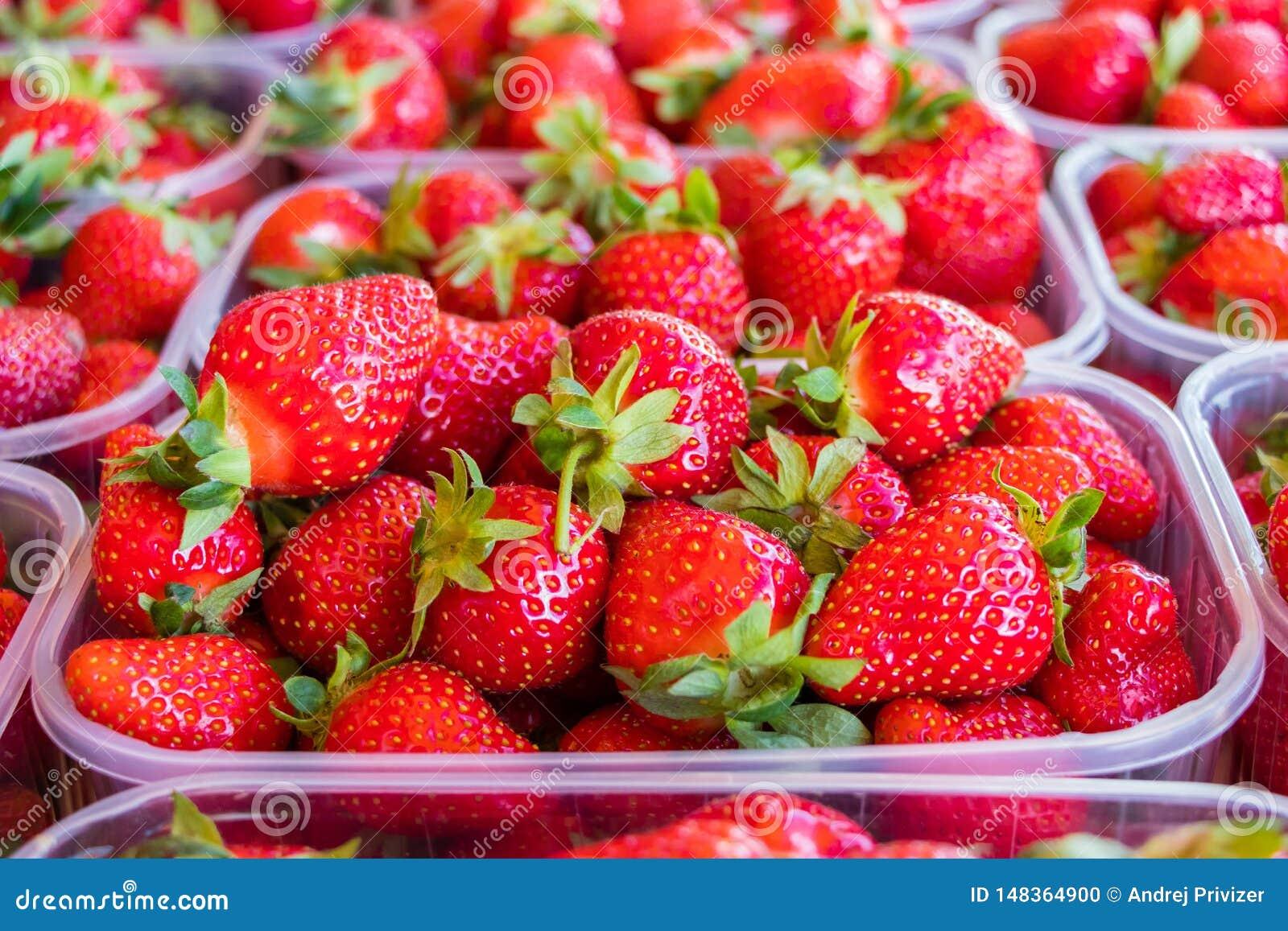 Fresh ripe strawberries in plastic boxes on market