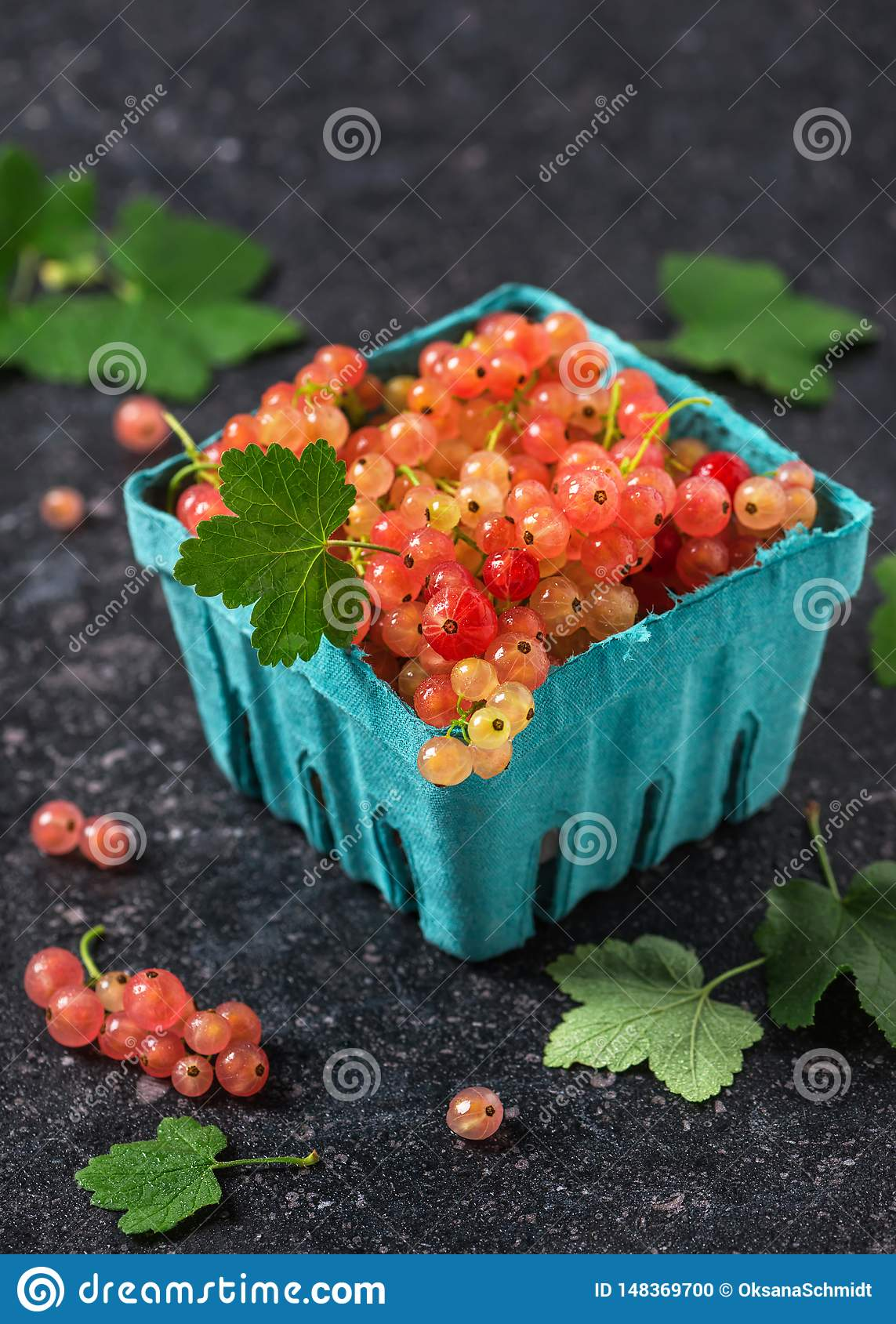 Fresh rosa and white currant berries with water drops in a turquoise cardboard box.