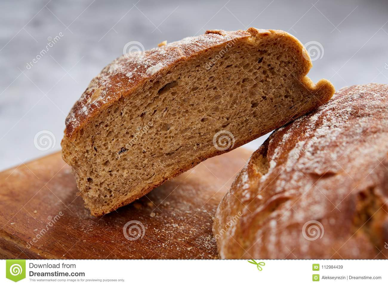 Fresh rye bread loaf on a wooden chopping board over white textured background, shallow depth of field
