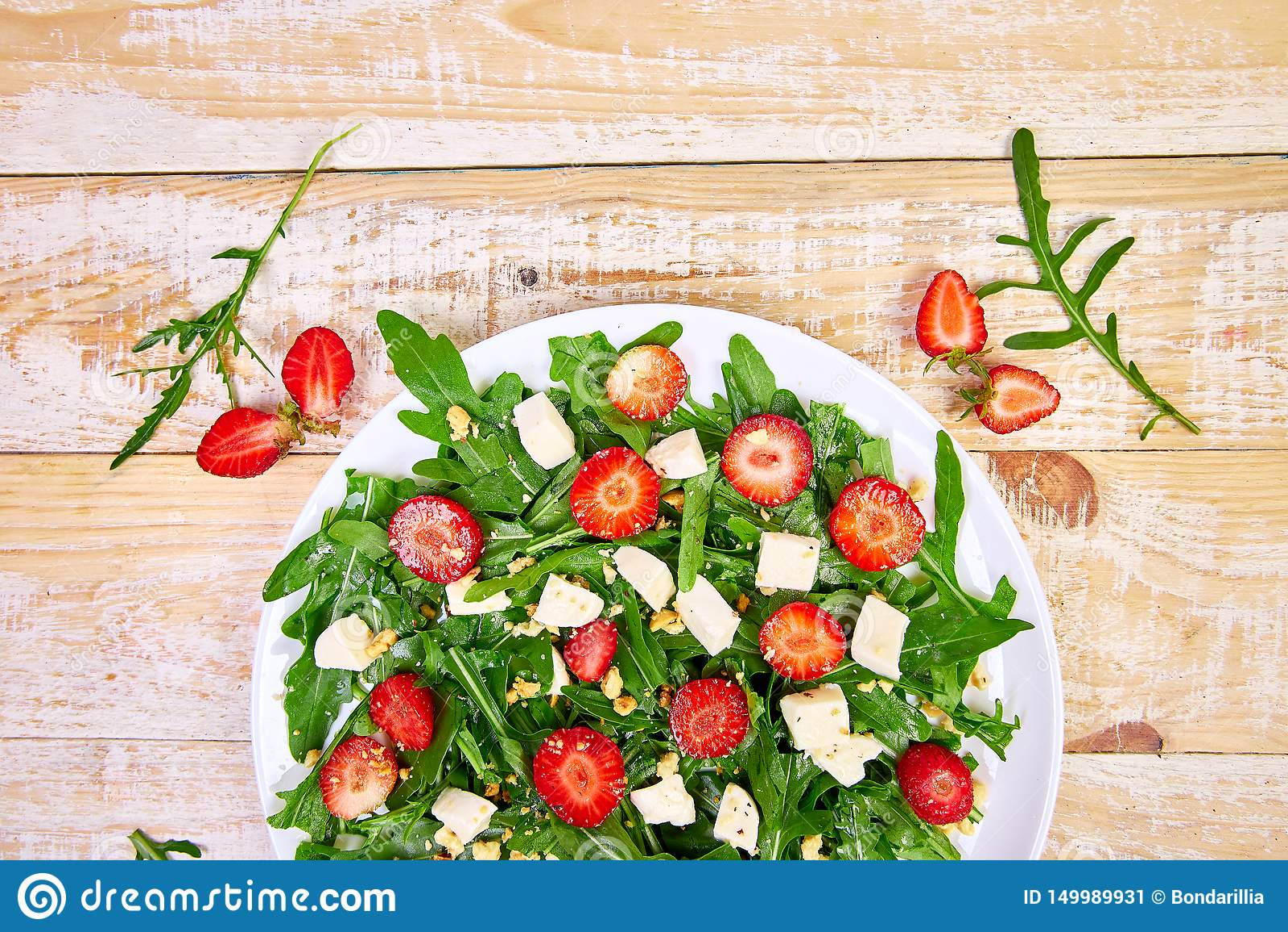 Fresh salad with arugula, strawberries, feta cheese and nuts