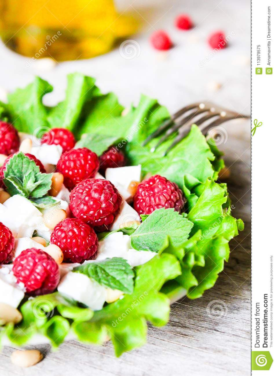 Fresh salad with feta cheese, raspberry, pine nuts and olive oil in a plate, selective focus