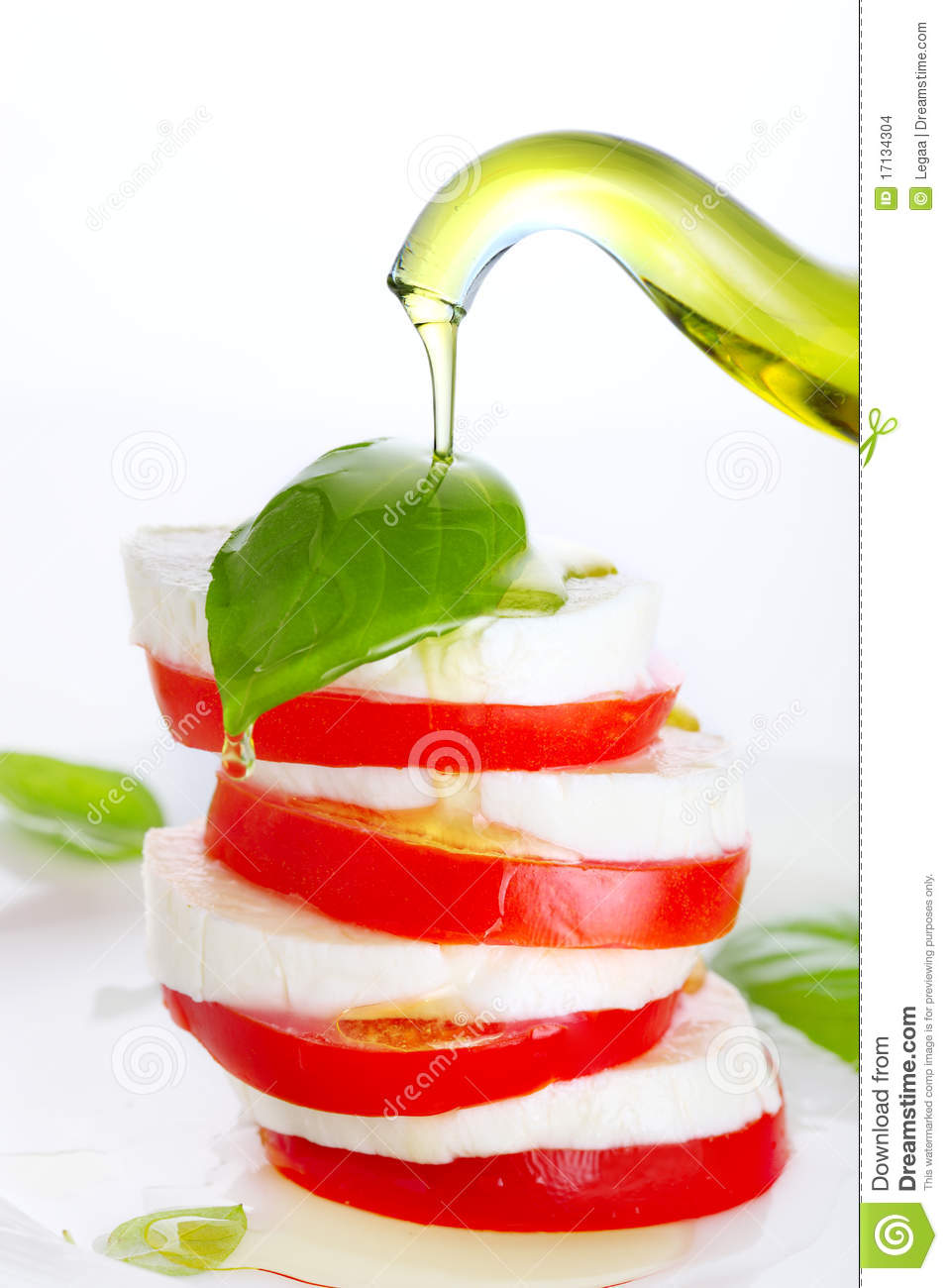 Fresh salad with mozzarella, tomato and basil with olive oil pouring ...