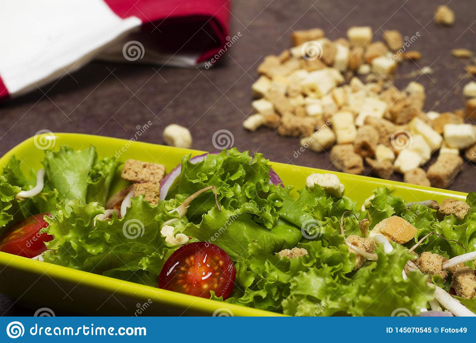 Fresh salad of tomato lettuce and onion with red striped cloth, bread laces and wooden spoon