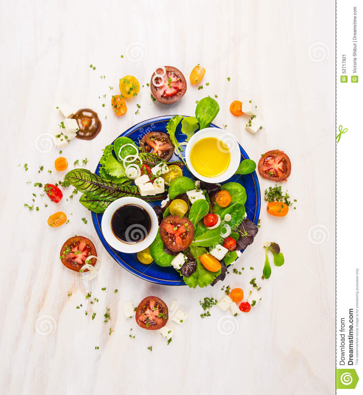 Fresh salad with tomatos,feta cheese, balsamic vinegar and oil in blue plate on white wooden background