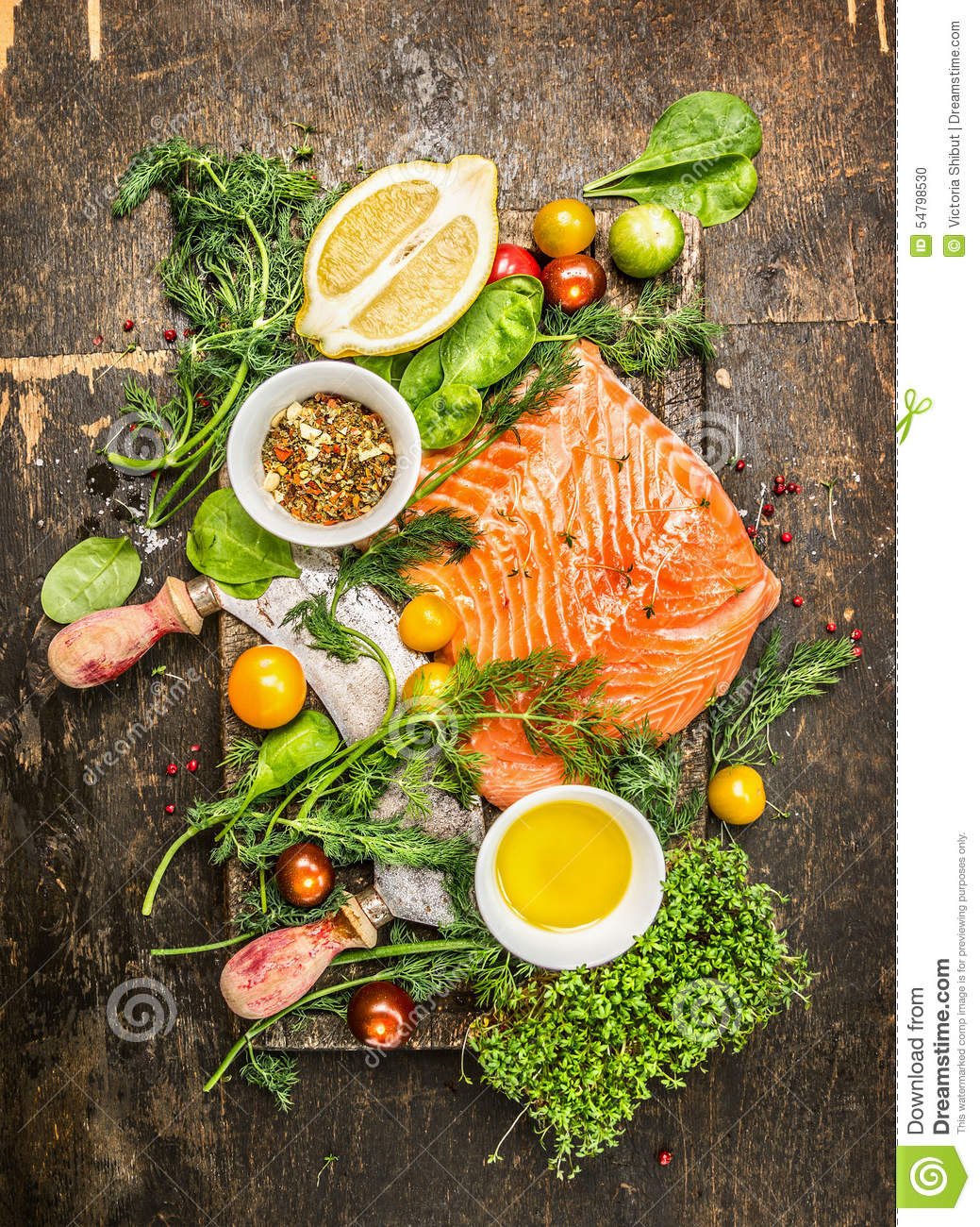 Fresh salmon fillet with fresh healthy herbs,vegetables, oil and spices on rustic wooden background