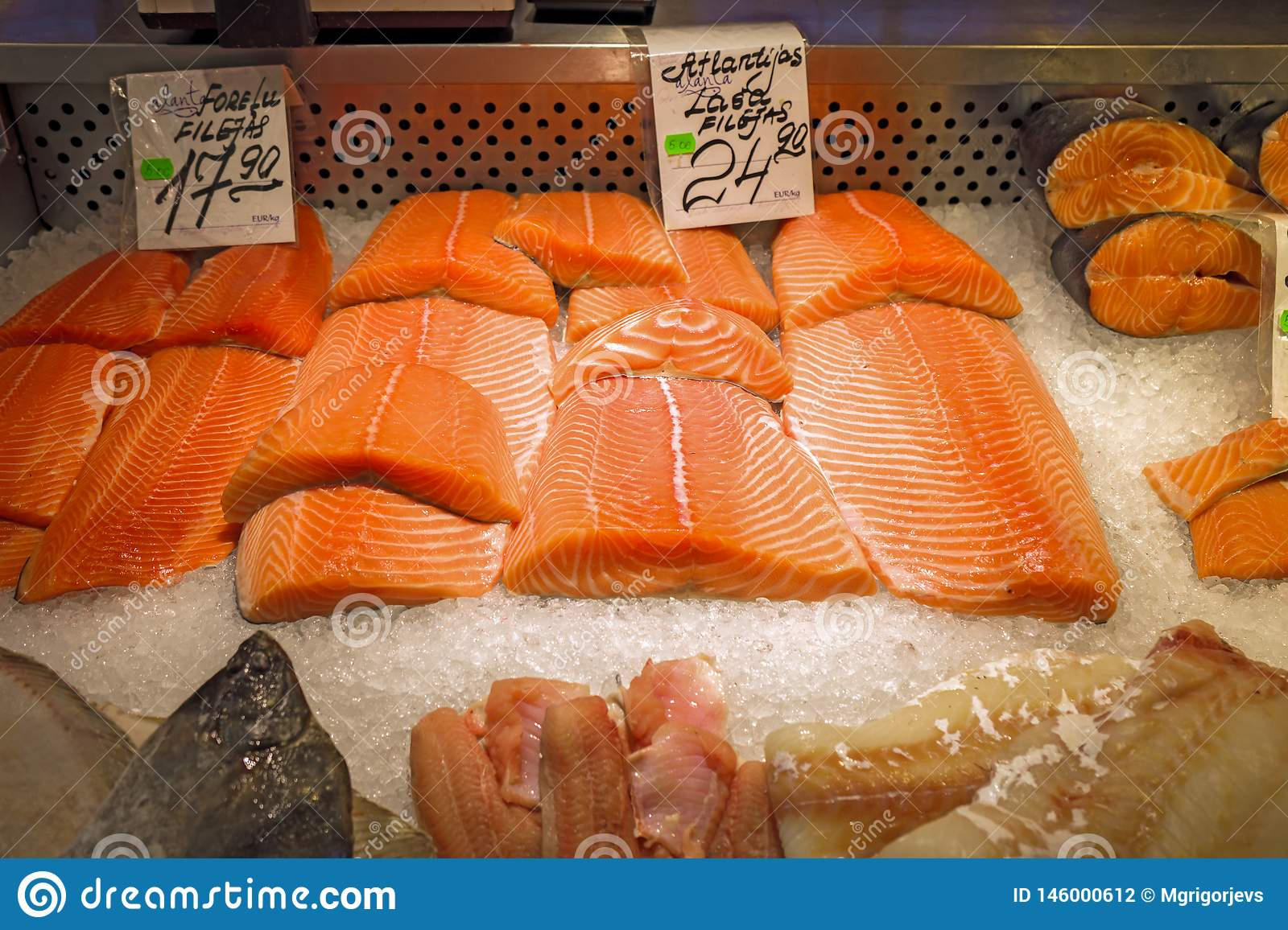 Fresh salmon fillets for sale on ice in supermarket store in fridge display. Red fish