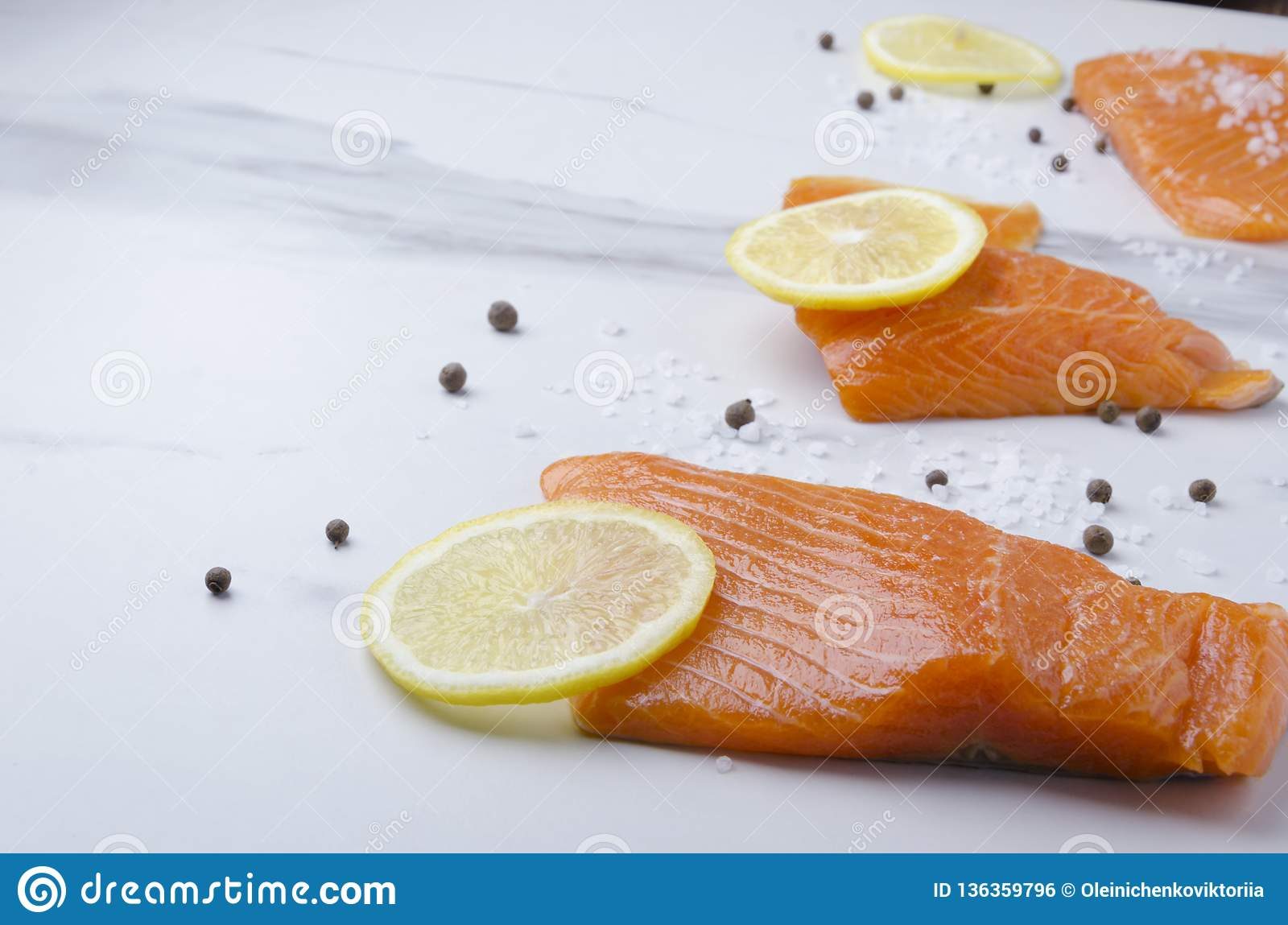 Fresh salmon with slices of lemon and pepper on marble table.Closeup of fish