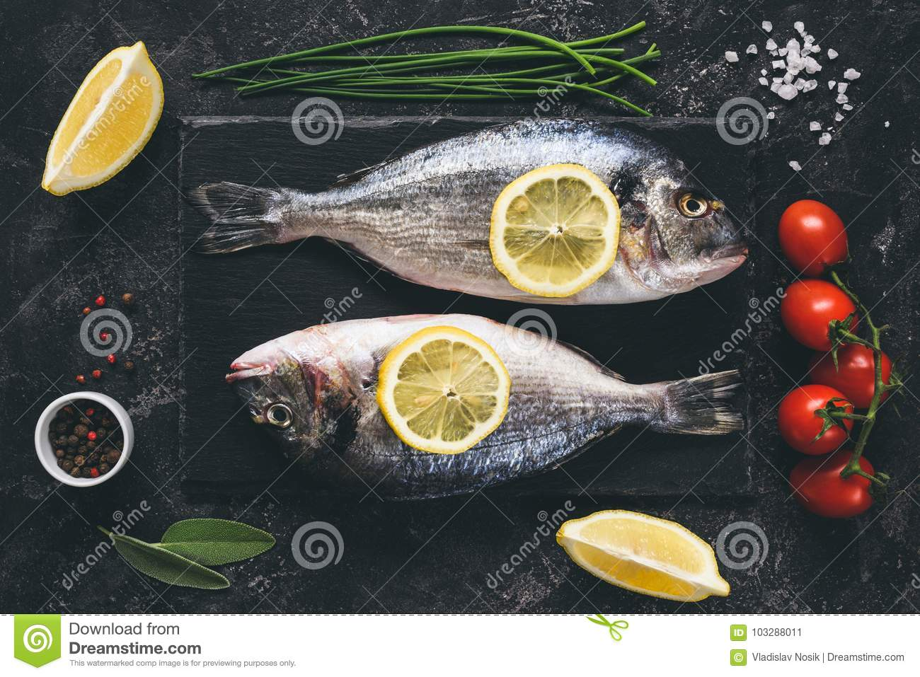 Fresh fish with spices, vegetables and herbs on slate background ready for cooking