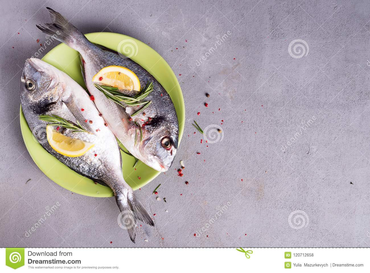 Fresh sea fish with spices and lemon ready for cooking on plate. Dorado or sea bream fish on stone background. Flat lay