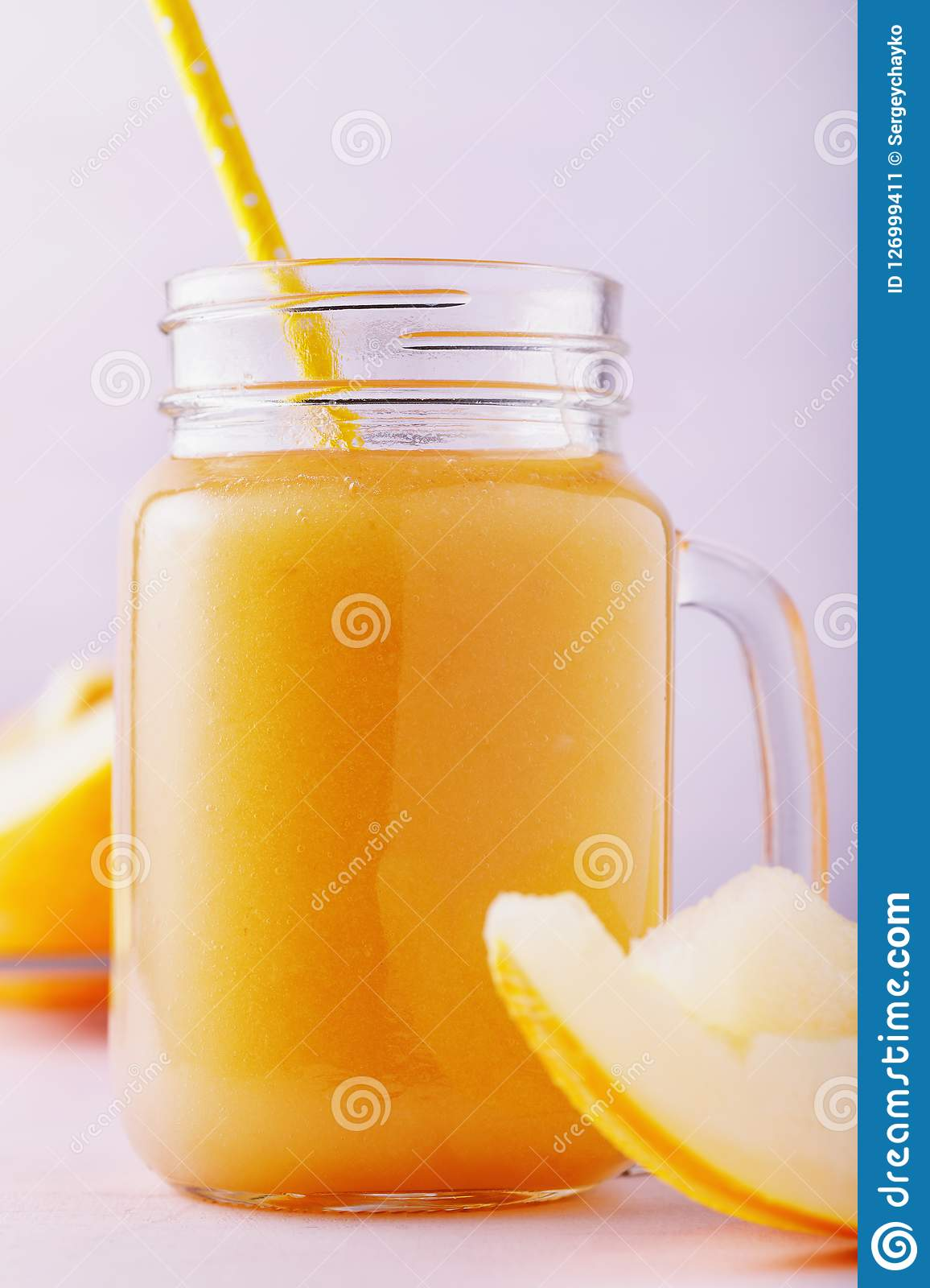 Fresh smoothie from ripe melon in a glass jar on wooden table