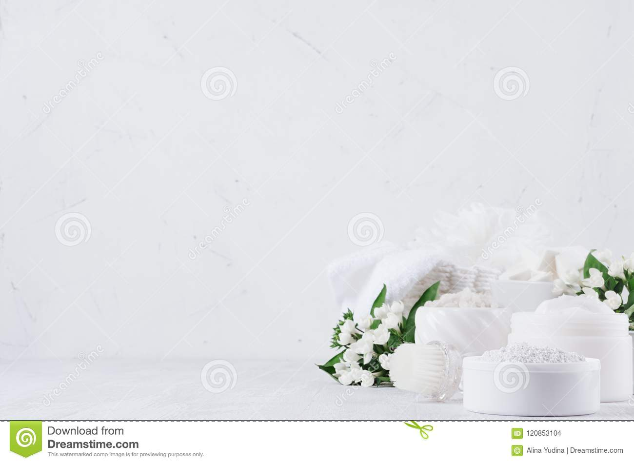 Fresh spring organic spa cosmetics products with small white flowers and green leaves on white wood background, copy space.