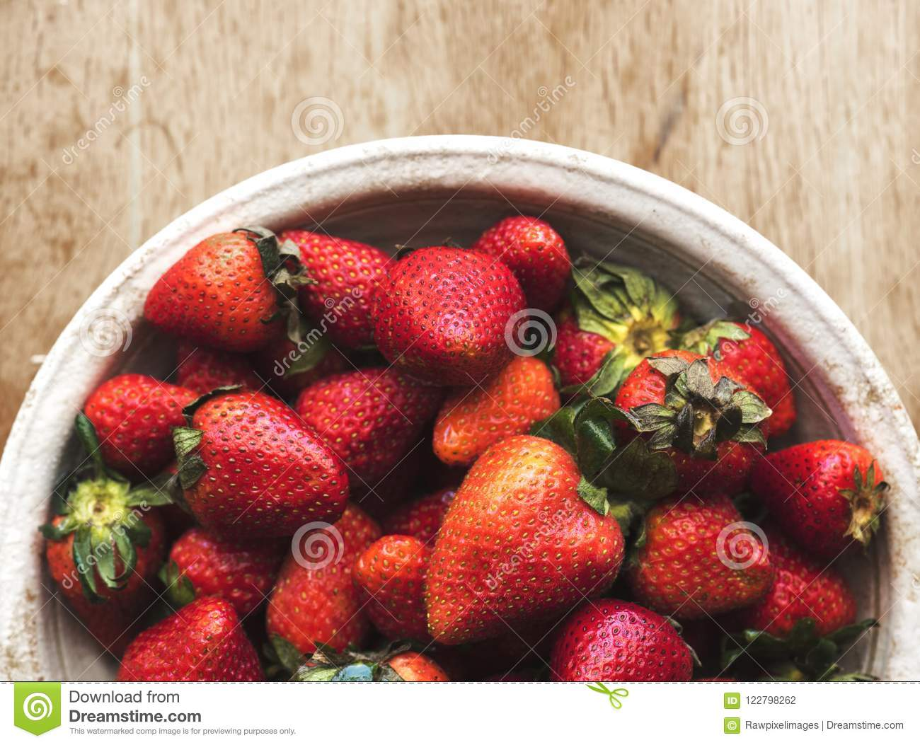 Fresh strawberries in a bowl on wooden table