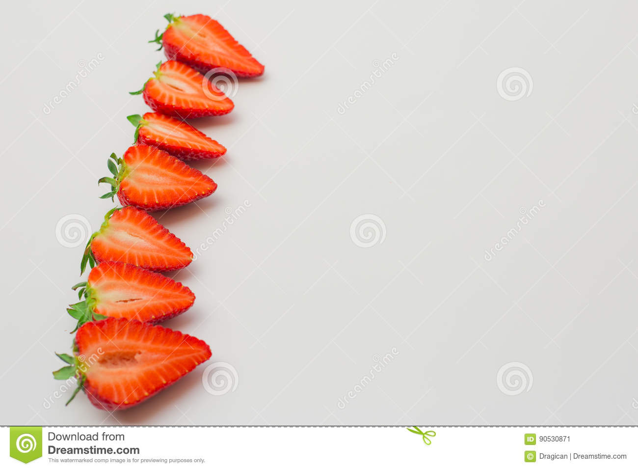 Fresh strawberries halved and arranged on a white background.