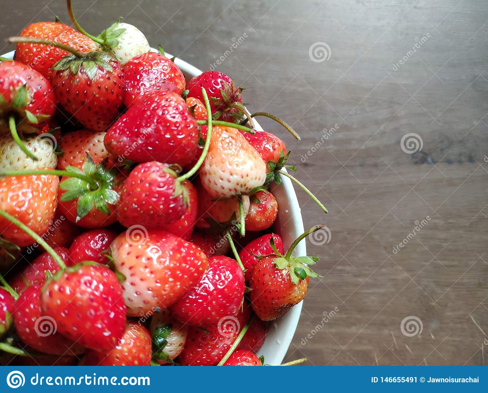 Fresh strawberries are in the white bowl on wooden table.
