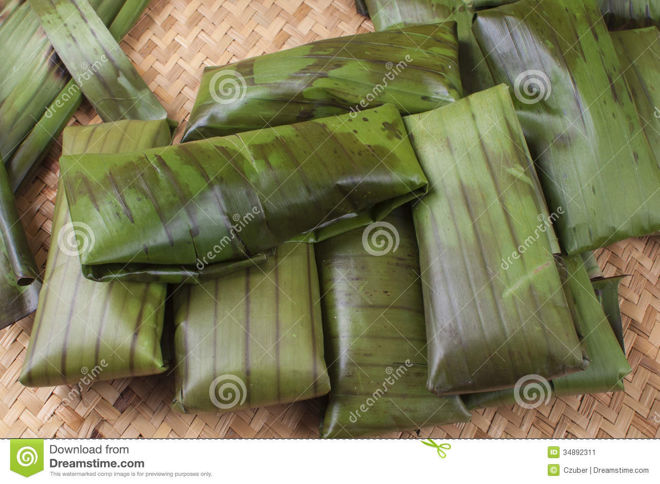 Pile of tamales freshly wrapped in banana leaves on palm woven mat ...