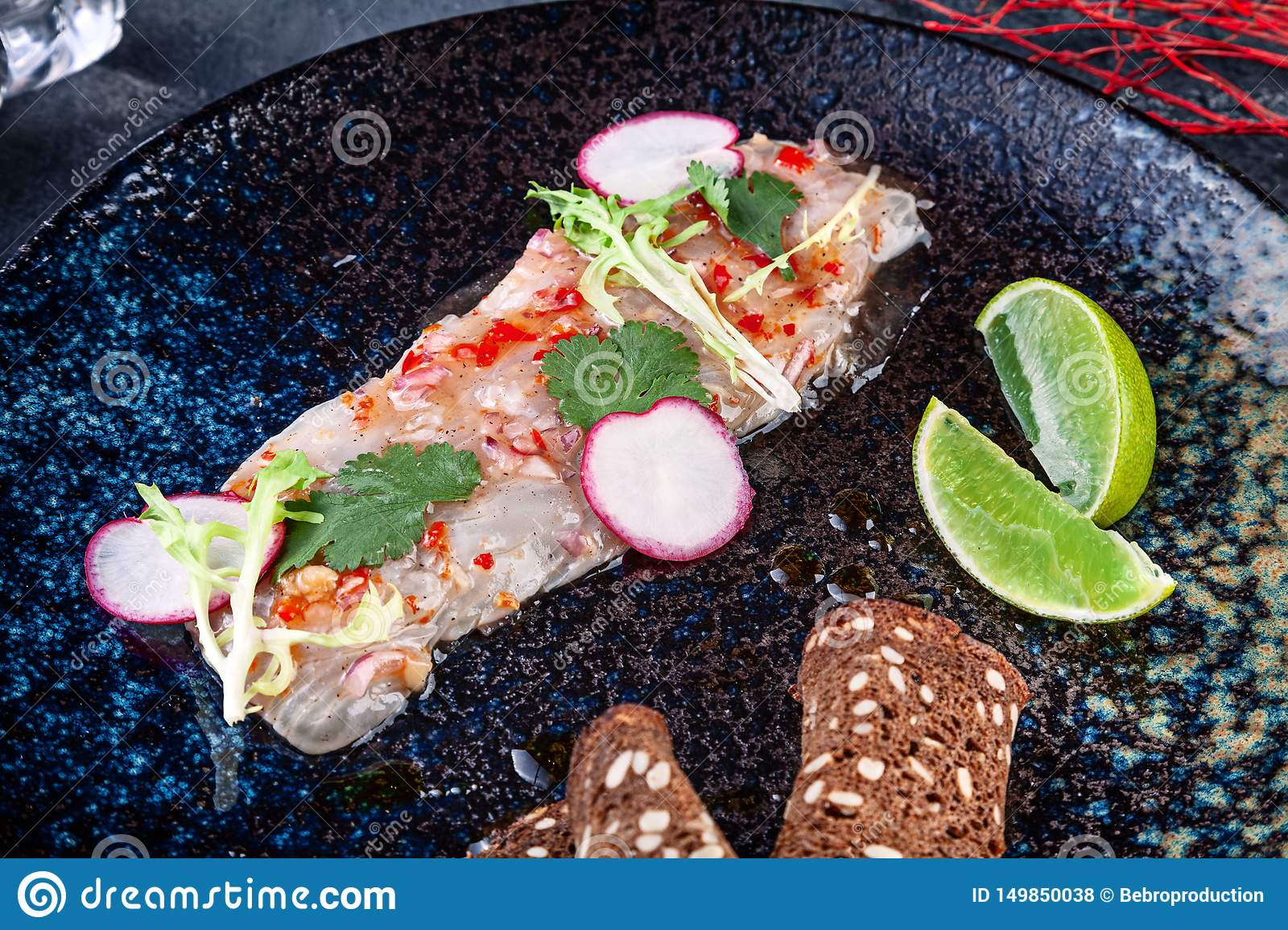 Fresh and tasty cebiche from seabass. seafood dish from raw fish. Ceviche with lime and microgreen served on dark plate. Cuisine
