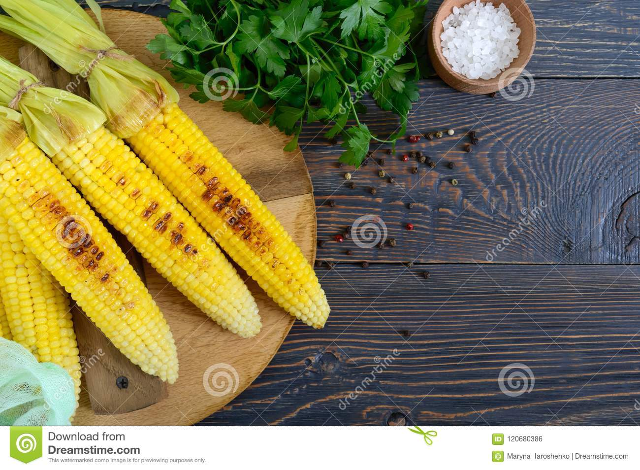 Fresh tasty grilled sweet corn with butter, sea salt and cilantro on a wooden table.