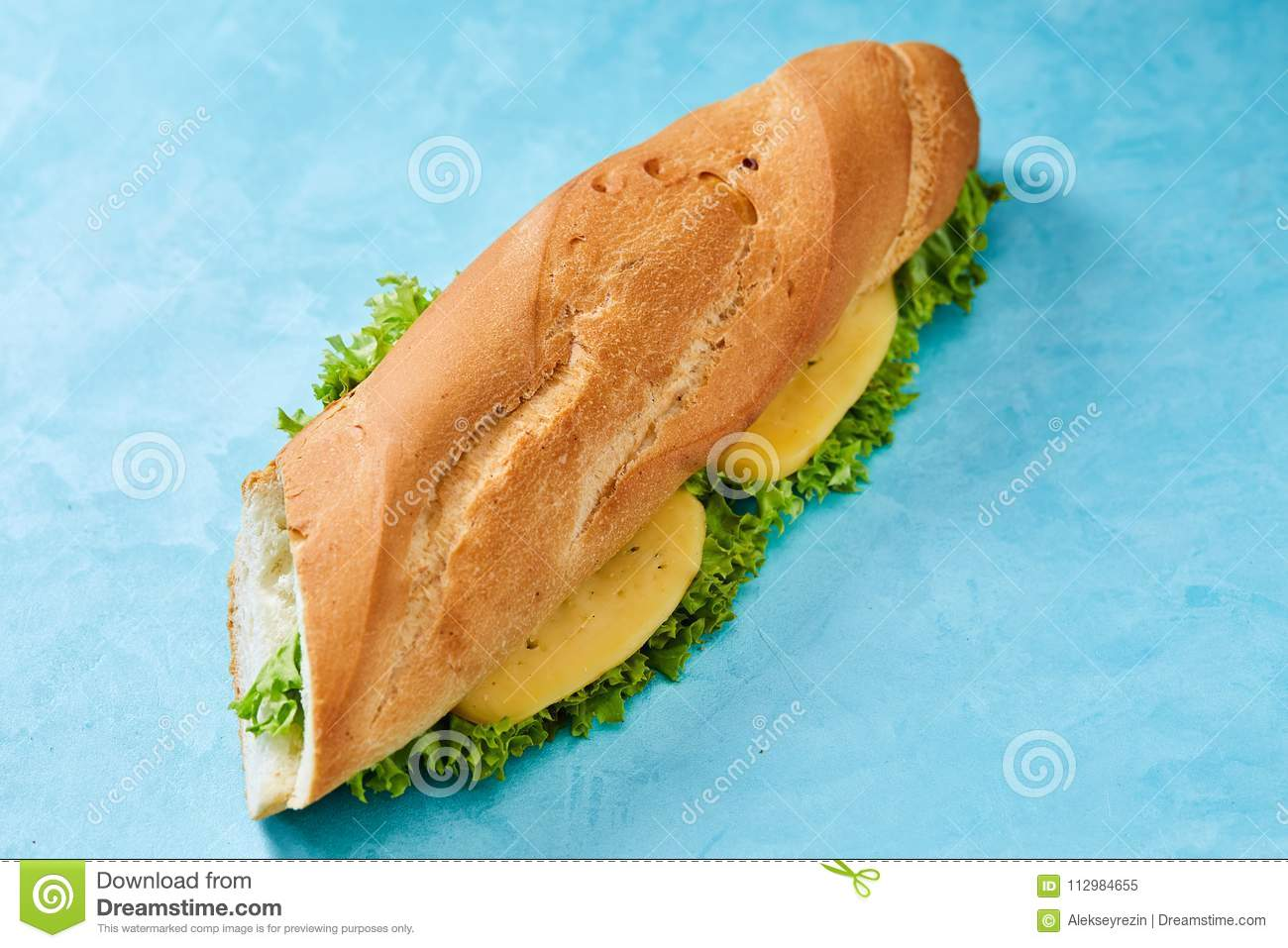 Fresh and tasty sandwich with cheese and vegetables on cutting board over blue background, selective focus.