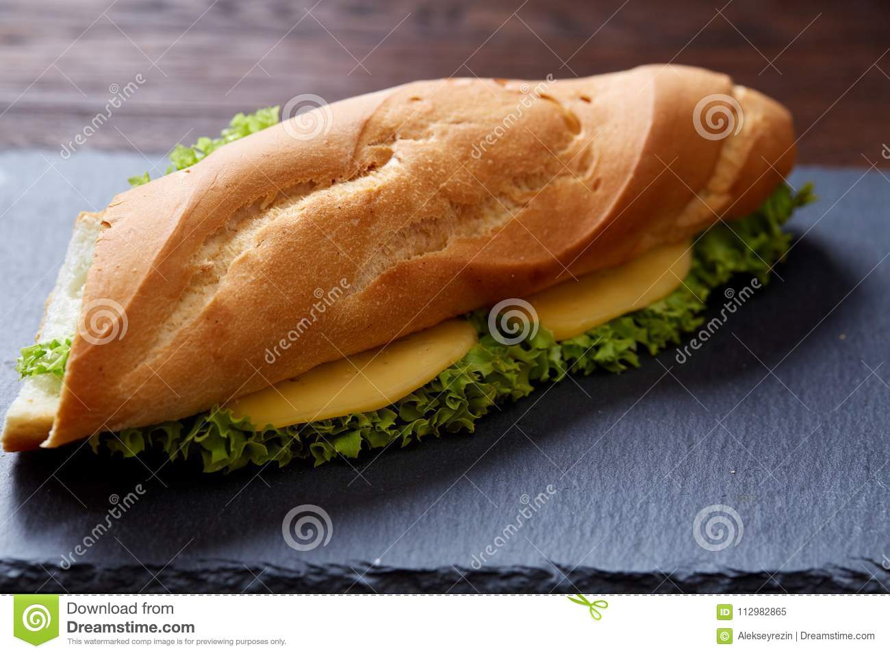 Fresh and tasty sandwich with cheese and vegetables on cutting board over white textured background, selective focus.