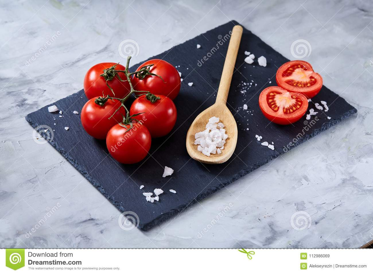 Fresh tomatoes and a spoon of salt on black stony board over white background, close-up, selective focus.