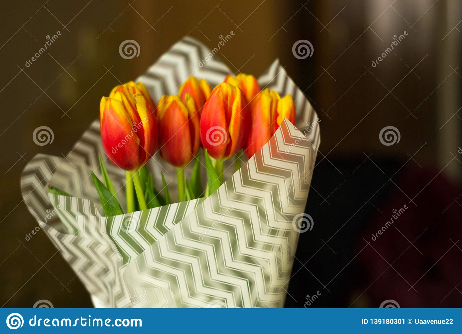 Fresh tulip flowers covered with white paper in vase on blurred background. Celebraiting holidays at home. Love present from