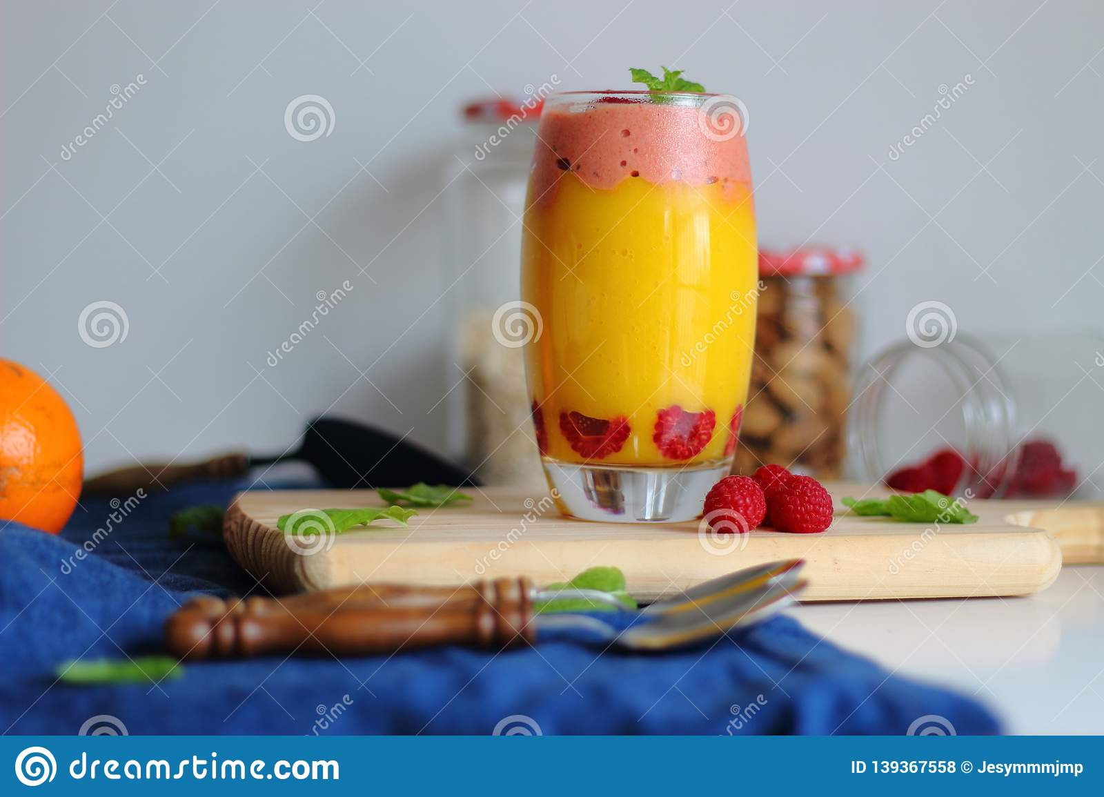 Fresh vegan layered dessert in a glass of colored smoothies of mango and orange with raspberries ice cream.