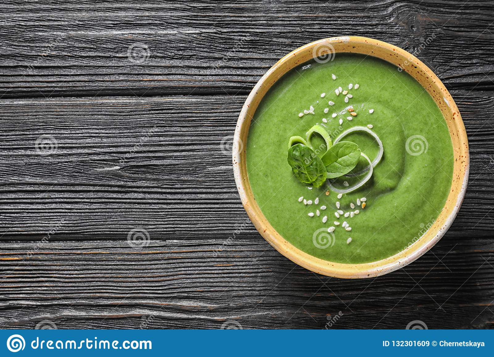 Fresh vegetable detox soup made of spinach in dish on wooden background, top view