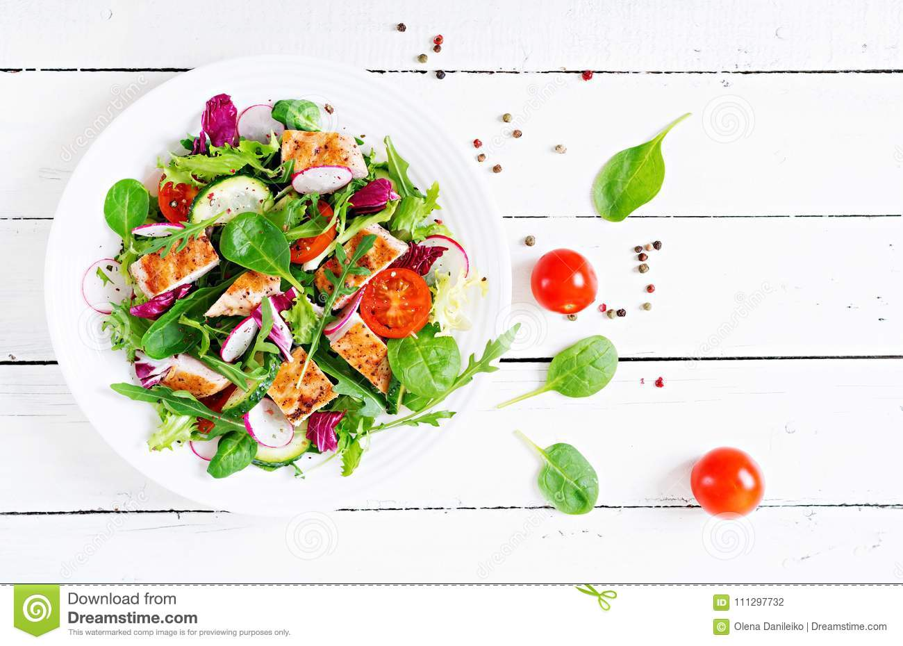 Fresh vegetable salad with grilled chicken breast - tomatoes, cucumbers, radish and mix lettuce leaves.
