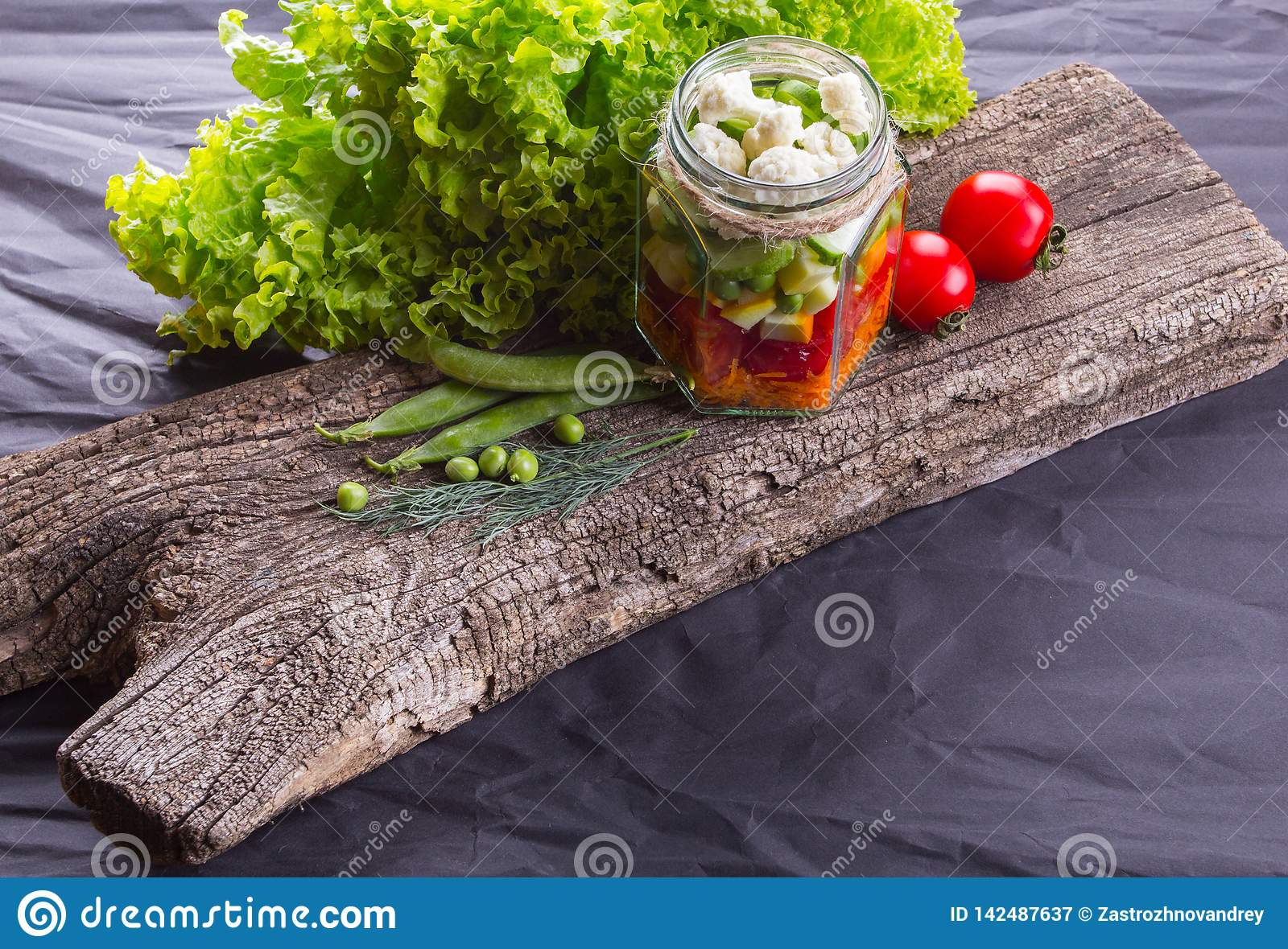Fresh vegetable salad with herbs on a wooden board, black textured background. With space for text. Healthy food