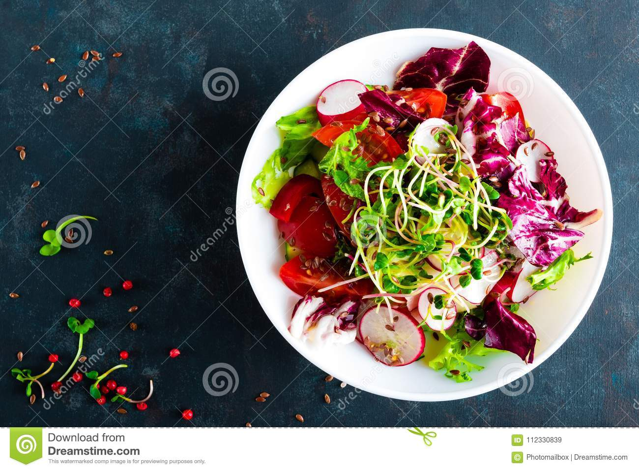 Fresh vegetable salad plate of tomatoes, italian mix, pepper, radish, green sprouts and flax seeds. Vegetarian dish, healthy food.
