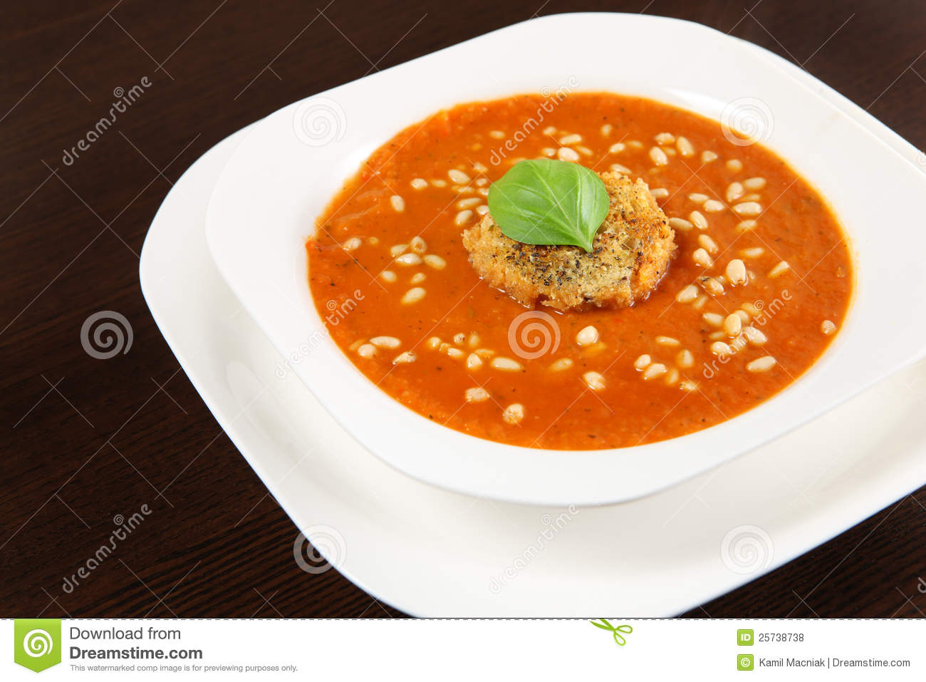 picture of a white bowl full of fresh vegetable cream soup with pine ...