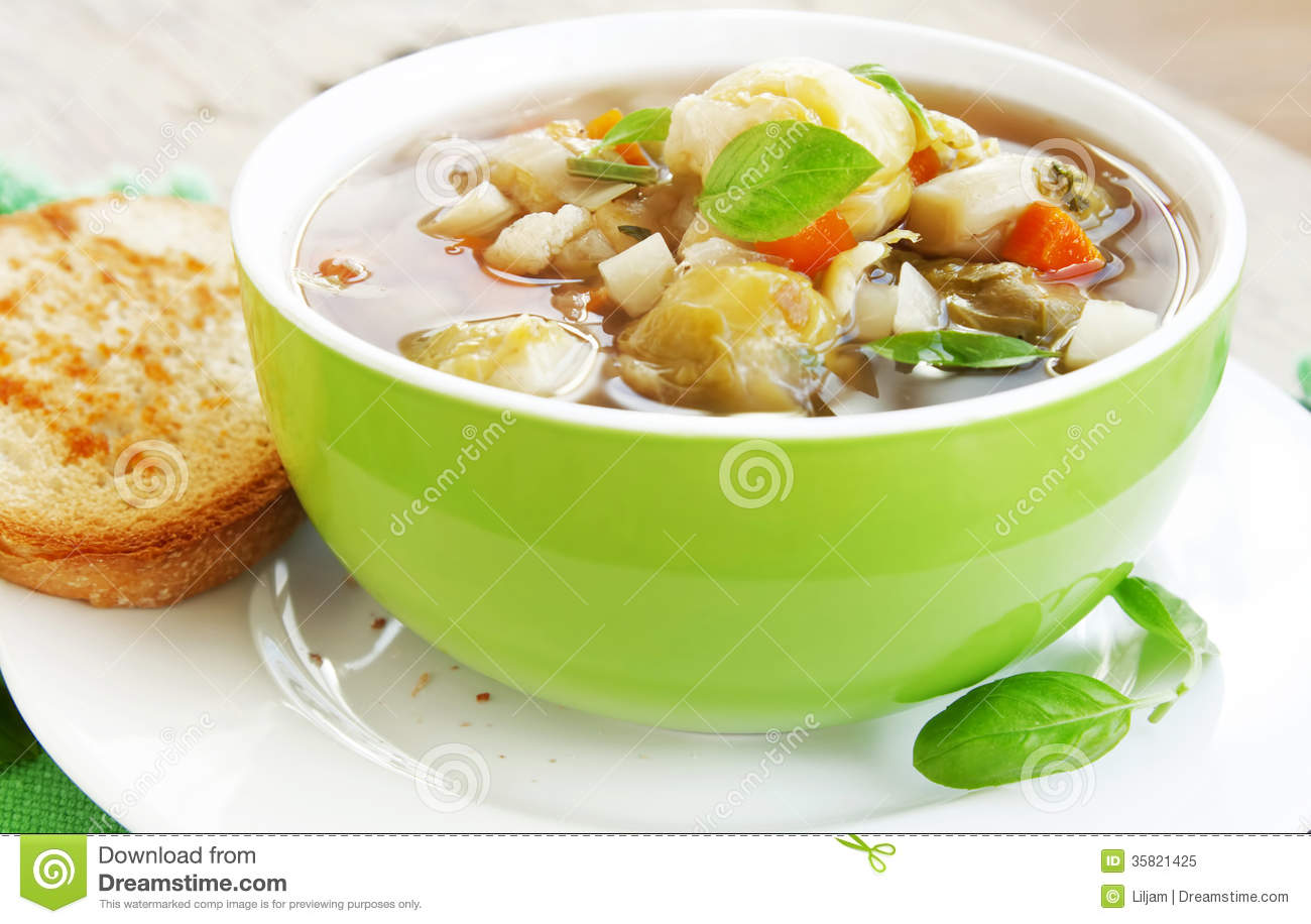 Green bowl of fresh vegetable soup with basil leaves,healthy meal.
