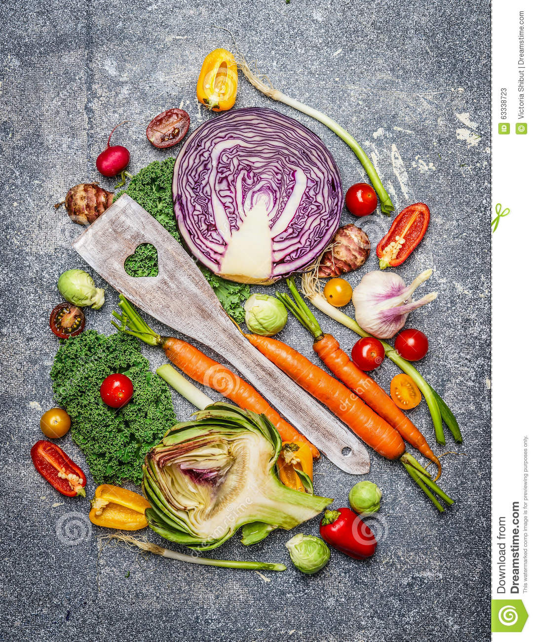 Fresh vegetables with cooking spoon composing on rustic background, top view.