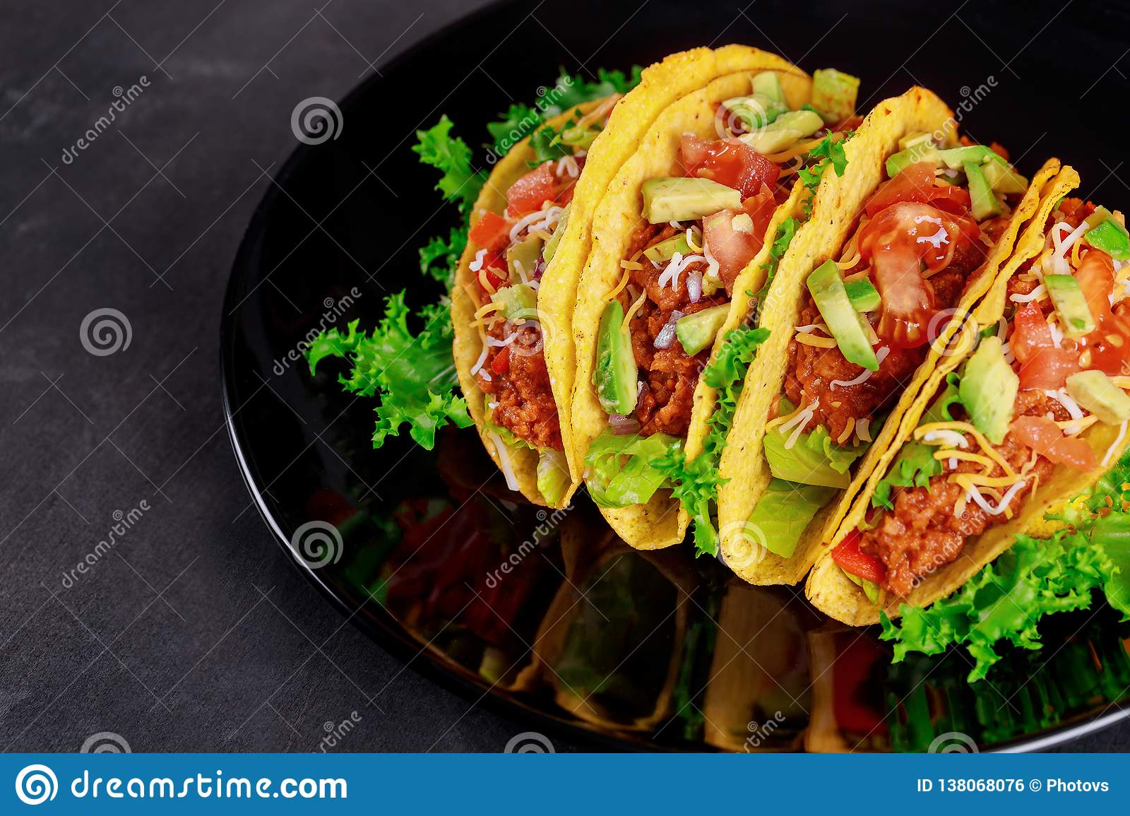 Fresh vegetables on a delicious tacos on black plate on wooden background