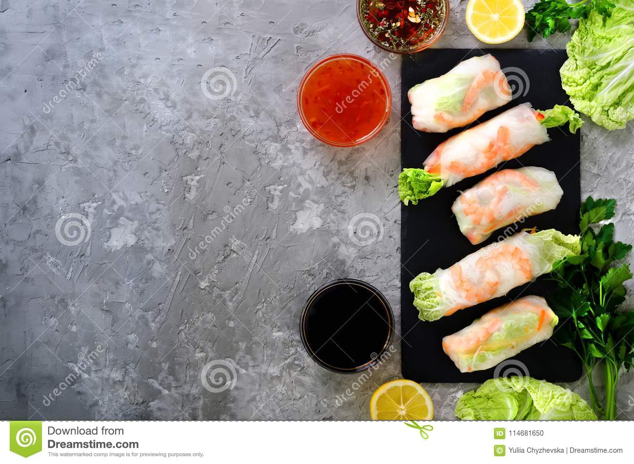 Fresh Vietnamese, Asian, Chinese food frame on grey concrete background. Spring rolls rice paper, lettuce, salad