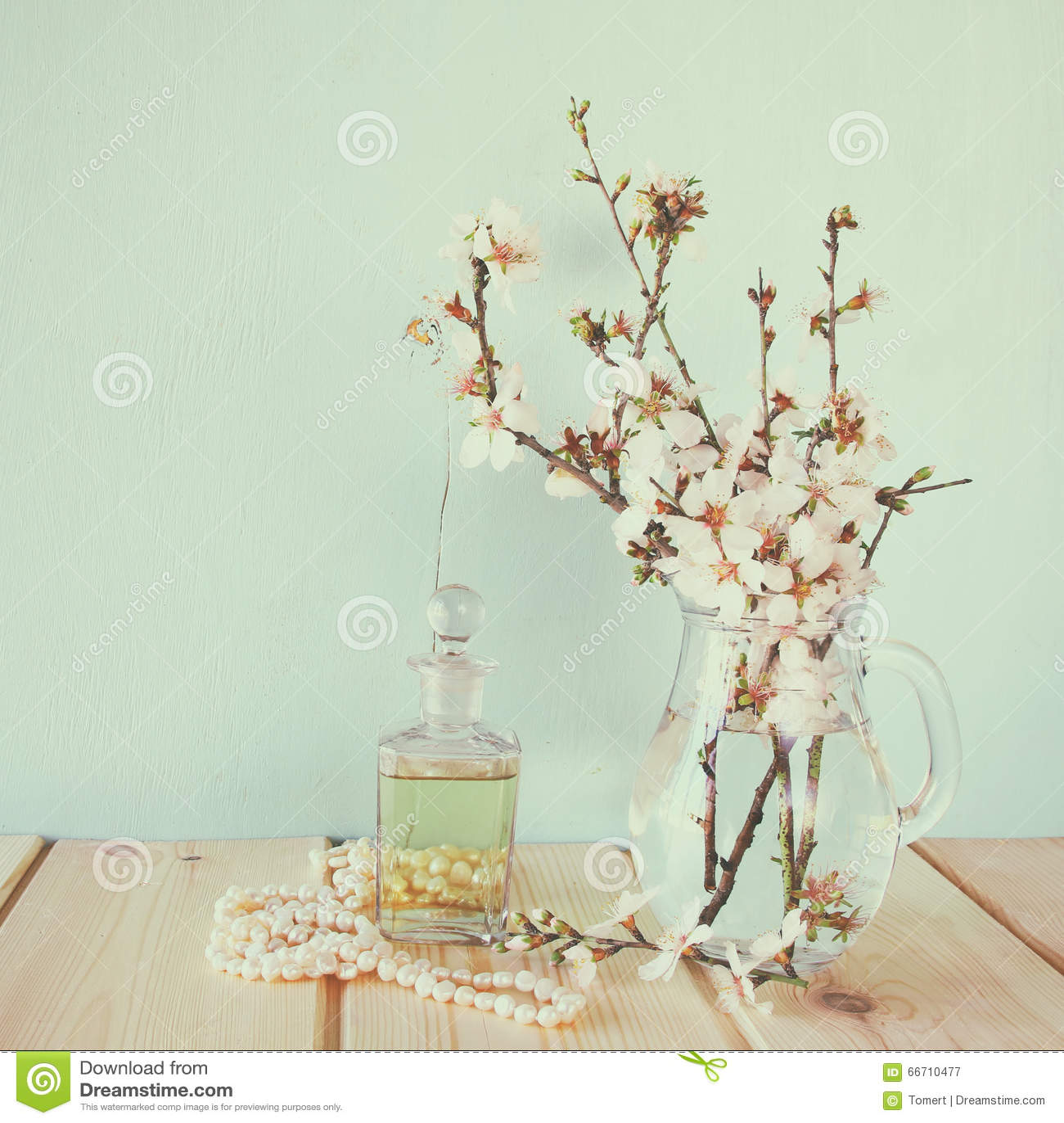 Fresh vintage perfume bottle next to white spring flowers on wooden download fresh vintage perfume bottle next to white spring flowers on wooden table vintage filtered mightylinksfo