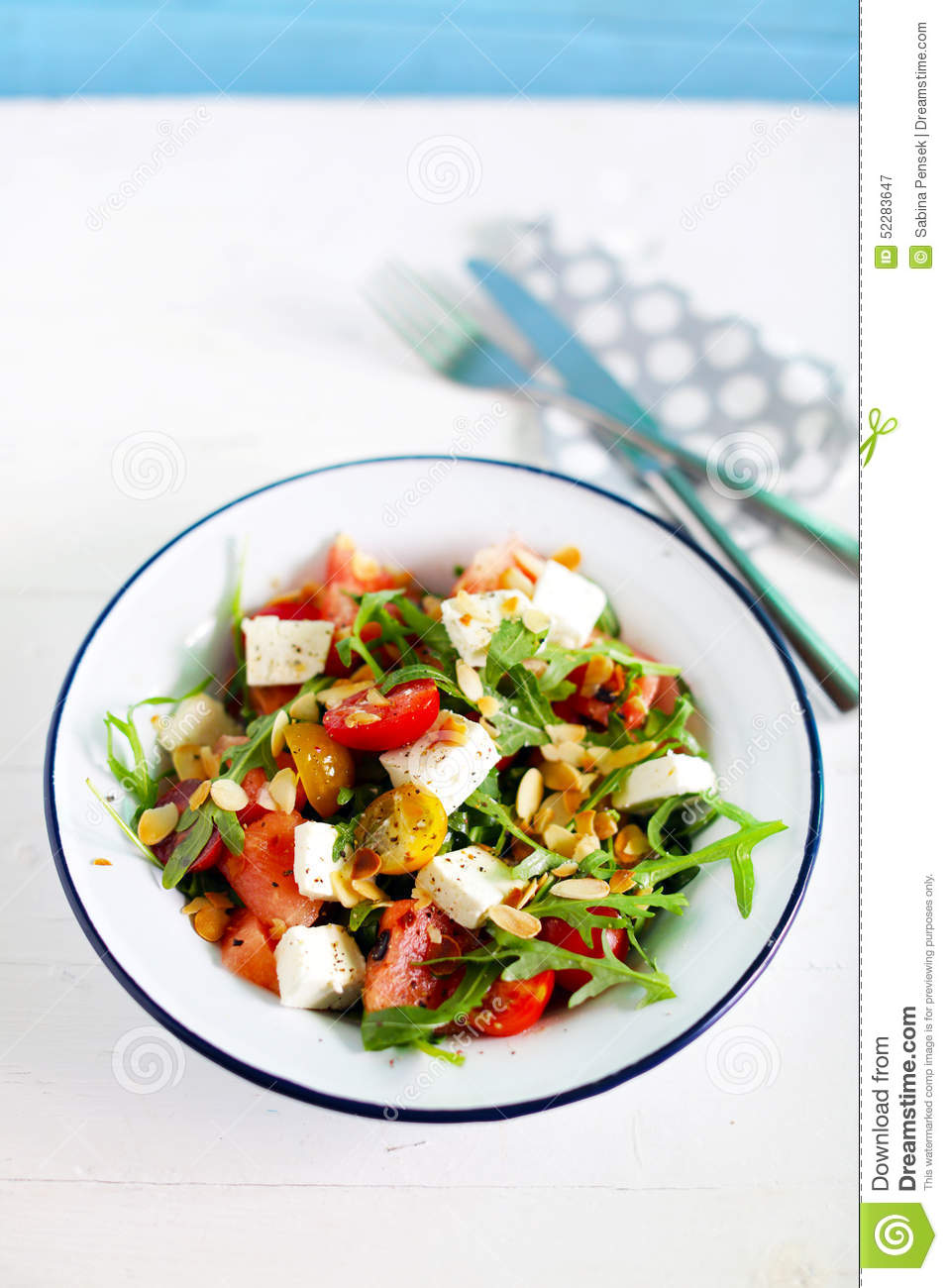 salad with arugula feta olives and tomato sliced with toasted almonds ...