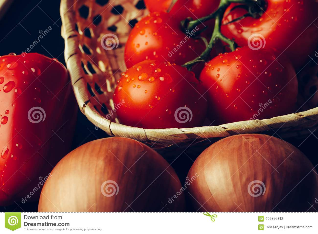 Fresh wet tomatoes in drops of water, golden onion, bell pepper on dark background
