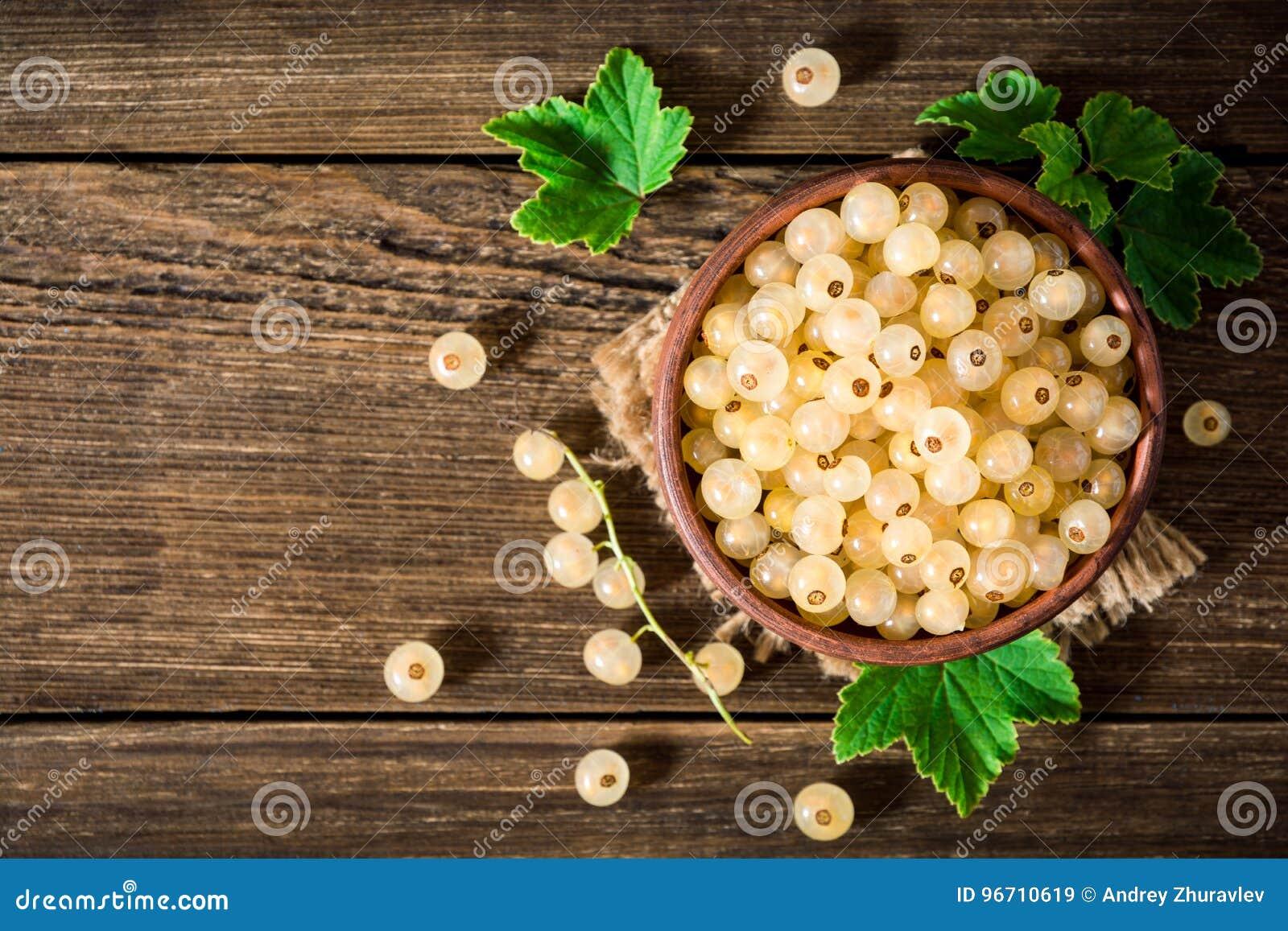 Fresh white currant in ceramic bowl on dark wooden background.