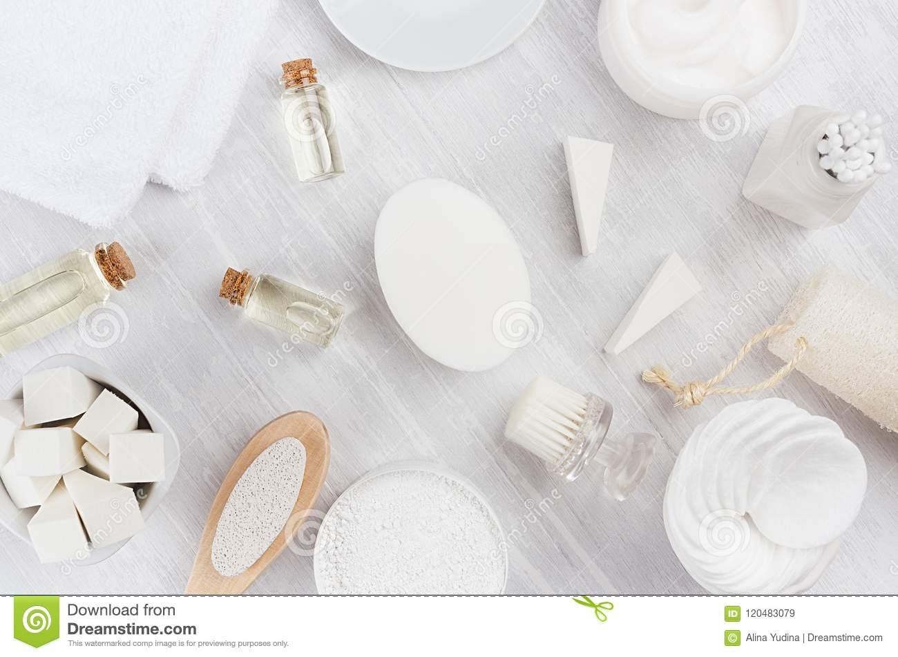 Fresh white natural cosmetics - white cream, oil, towel and bath accessories on soft light white wood table, flat lay.
