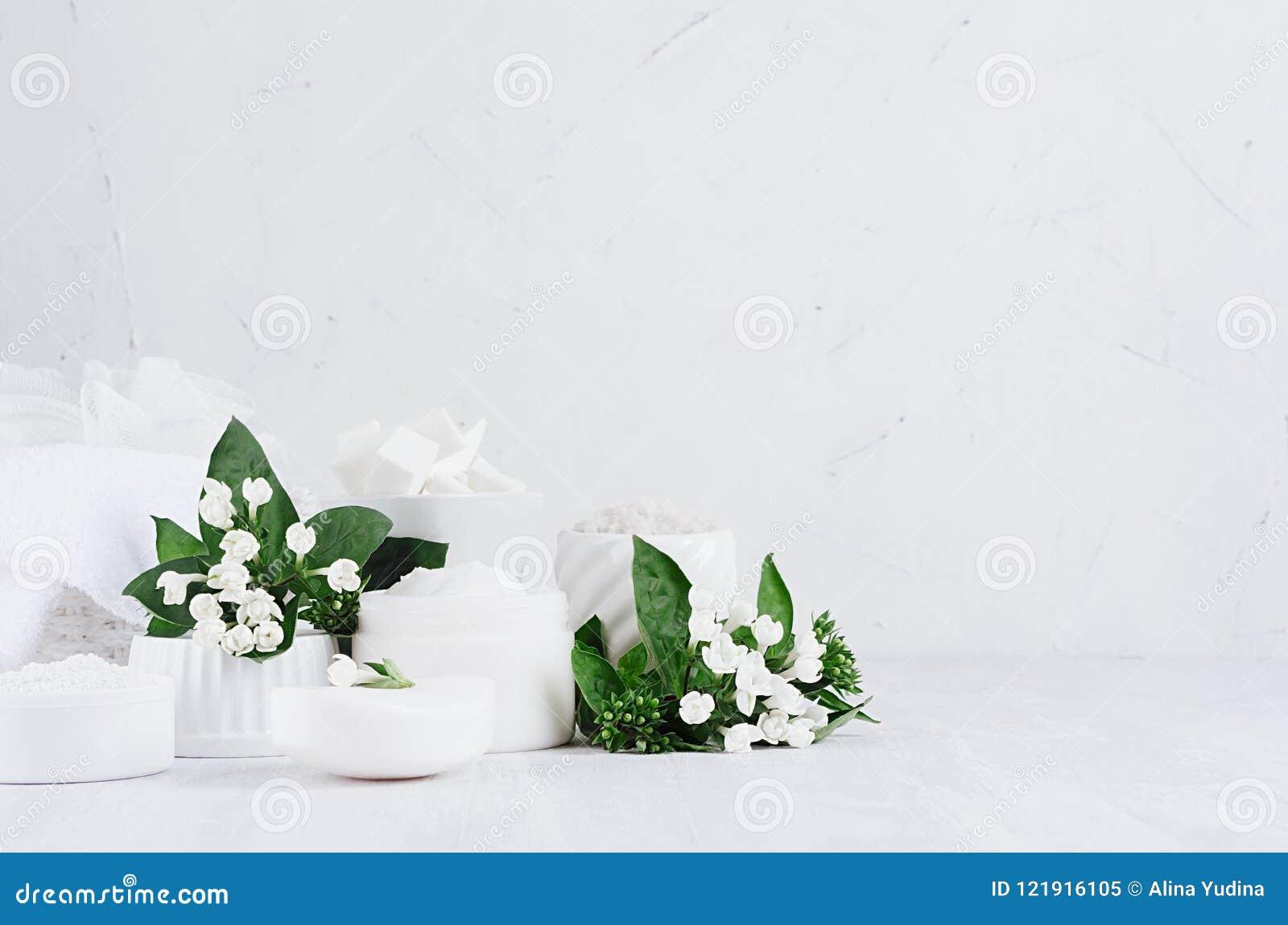 Fresh white natural wedding cosmetics - white cream, salt, clay, towel, bath accessories, flowers on soft light white wood table.