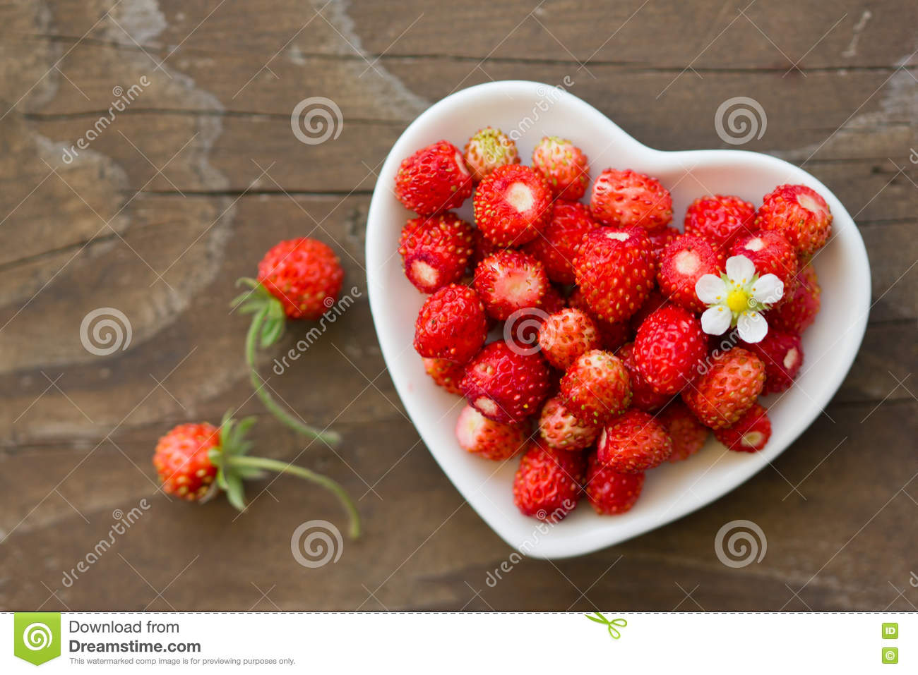 Fresh wild strawberries in a cup in the shape of a heart symbol royalty free stock photo biocorpaavc