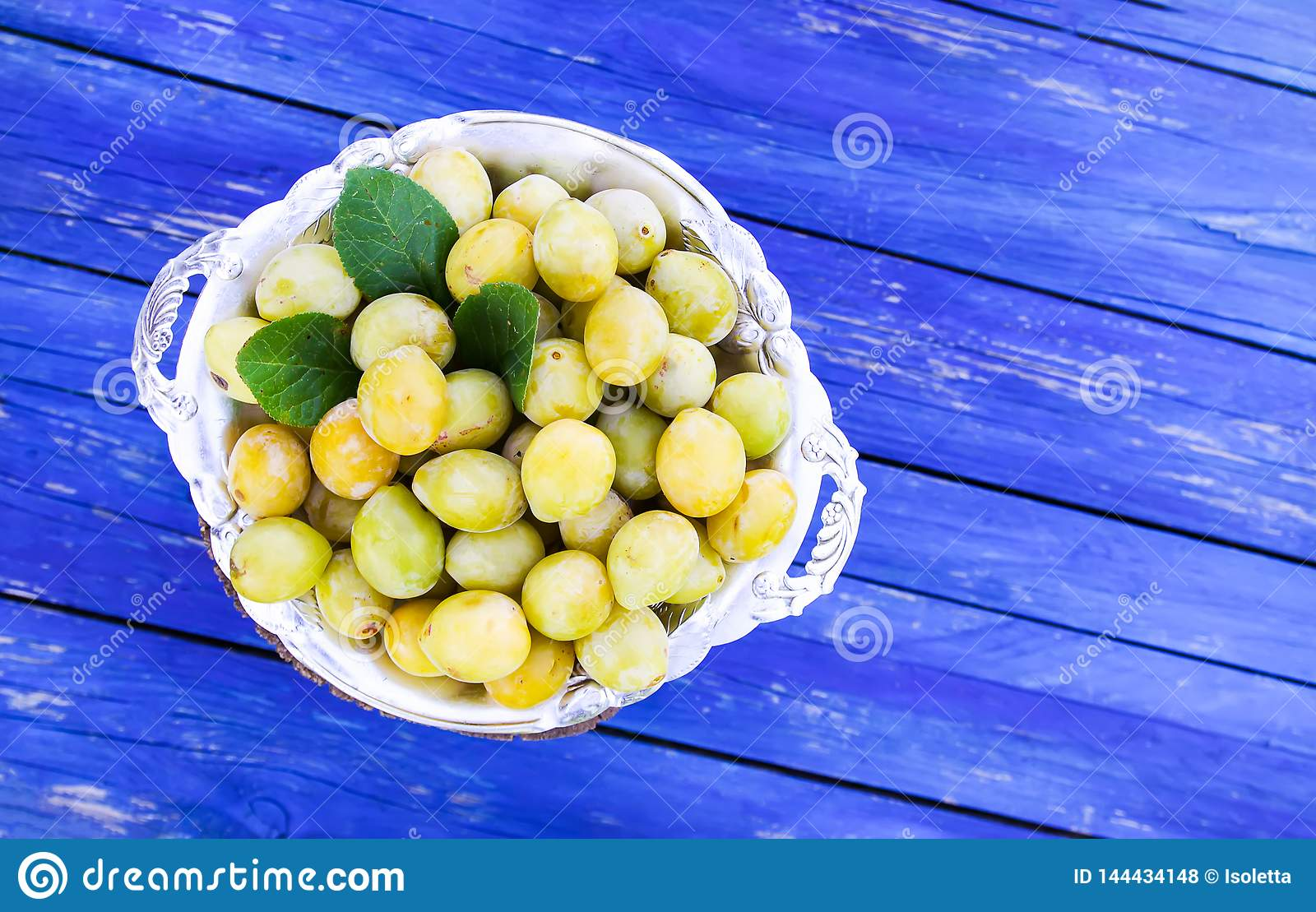 Fresh yellow plums. Ripe fruits in a plate on blue boards background