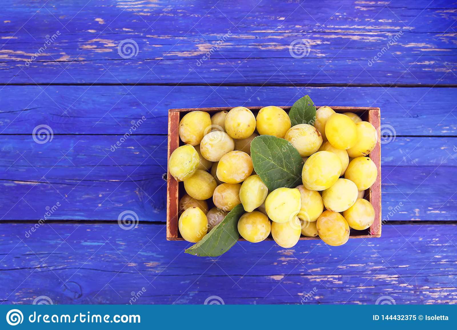 Fresh yellow plums. Ripe fruits in a wooden box on blue boards